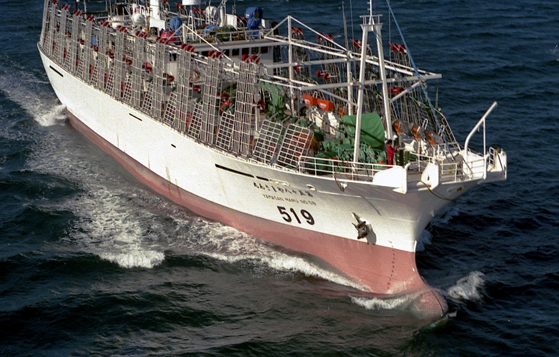 Image of large commercial fishing vessel using longliner techniques to catch fish, similar to those used in this study. Vessel is red and white coloring loaded with fishing equipment on deck and moving through open waters.