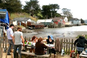People enjoy outdoor dining by sea