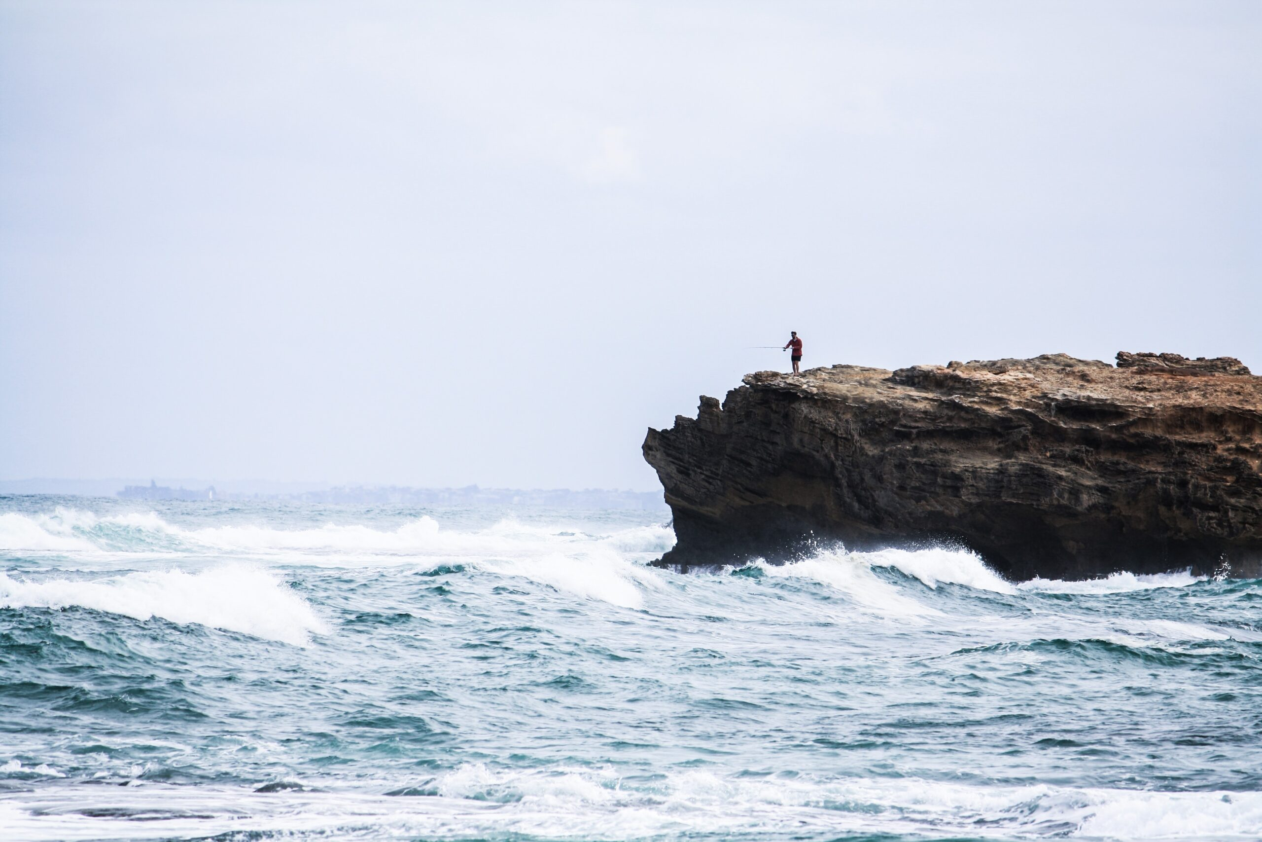 Solo human casts fishing line into sea from a rocky cliff