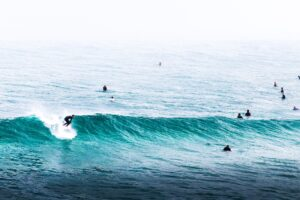 Surfers catching waves in a teal sea