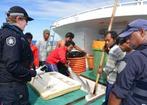 Officials and fishers inspect catch on a fishing vessel.