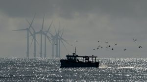 Fishing boat in front of wind turbines