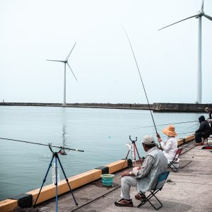 Two recreational anglers in front of wind turbines on shore